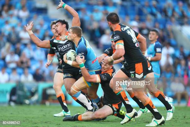 Dale Copley of the Titans is tackled during the round 21 NRL match between the Gold Coast Titans and the Wests Tigers at Cbus Super Stadium on July...
