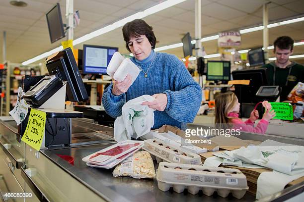 Dale Danahy one of the owners of Colella's Supermarket bags groceries while working the register at the store in Hopkinton Massachusetts US on...
