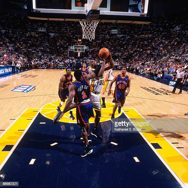 Dale Davis of the Indiana Pacers and Larry Johnson of the New York Knicks get tangled up on a fast break in Game Two of the Eastern Conference Finals...