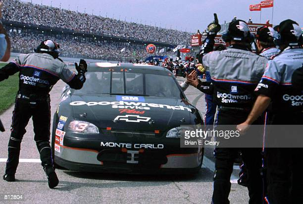 Dale Earnhardt driver of the GM Goodwrench Chevrolet drives down pit road to celebrate with his pit crew after winning the Winston Cup Diehard 500 on...