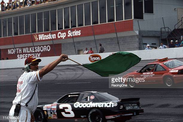 Dale Earnhardt heads for his pit as the pit lane flagman waves the green flag indicating pit road is open during a caution flag period in a NASCAR...