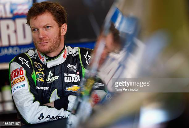 Dale Earnhardt Jr driver of the AMP Energy Gold / 7Eleven Chevrolet looks on in the garage area during practice for the NASCAR Sprint Cup Series AAA...