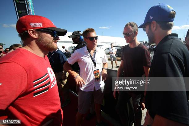 Dale Earnhardt Jr driver of the AXALTA Chevrolet and Jimmie Johnson driver of the Lowe's Chevrolet talk with Tour de France champion Chris Froome...