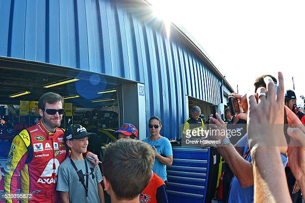 Dale Earnhardt Jr driver of the Axalta Chevrolet poses for photos with fans during practice for the NASCAR Sprint Cup Series FireKeepers Casino 400...