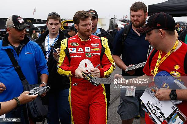 Dale Earnhardt Jr driver of the Axalta Chevrolet signs autographs for fans in the garage area during practice for the NASCAR Sprint Cup Series Axalta...
