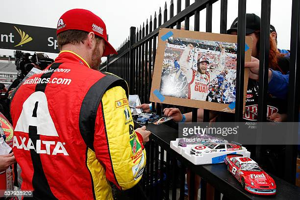 Dale Earnhardt Jr driver of the Axalta Chevrolet signs autographs for fans during qualifying for the NASCAR Sprint Cup Series Axalta 'We Paint...