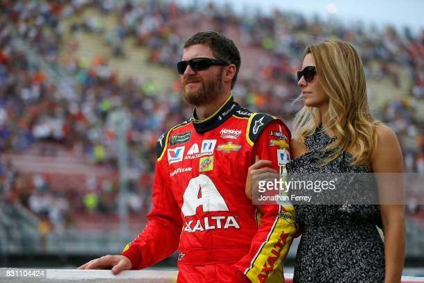 Dale Earnhardt Jr driver of the Axalta Chevrolet stands on the grid with his wife Amy Reimann prior to the Monster Energy NASCAR Cup Series Pure...