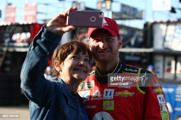 Dale Earnhardt Jr driver of the Axalta Chevrolet takes a selfie with a fan during practice for the Monster Energy NASCAR Cup Series O'Reilly Auto...