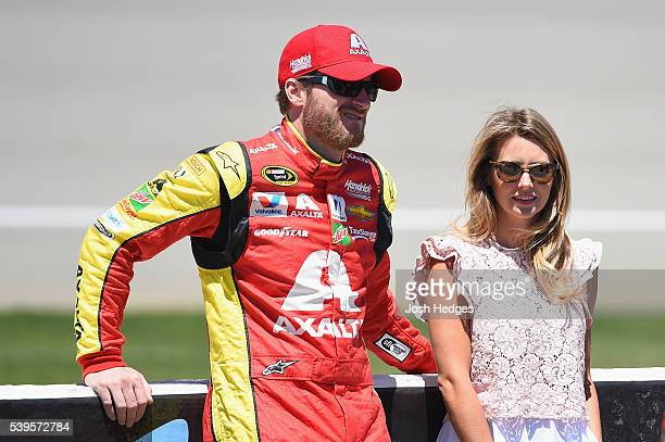 Dale Earnhardt Jr driver of the Axalta Chevrolet talks to fiance Amy Reimann on the grid prior to the NASCAR Sprint Cup Series FireKeepers Casino 400...