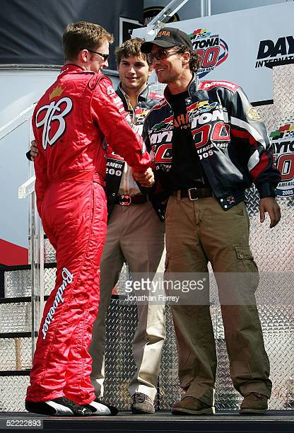 Dale Earnhardt Jr driver of the Budweiser Chevrolet meets actors Ashton Kuchter and Mathew McConaughey during prerace driver introductions for the...