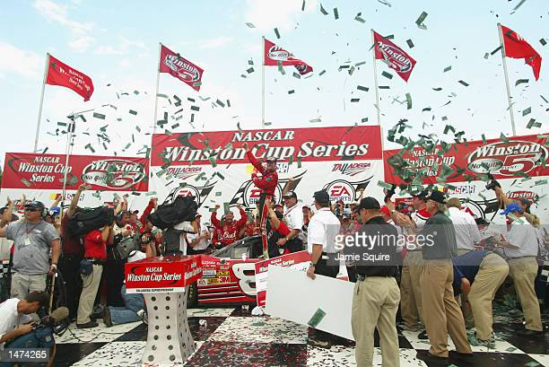 Dale Earnhardt Jr driver of the Budweiser Chevrolet Monte Carlo celebrates in victory lane after winning the NASCAR Winston Cup EA Sports 500 at...