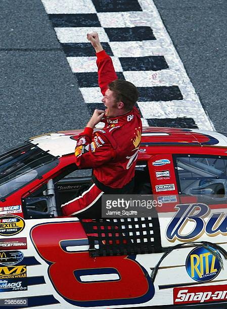 Dale Earnhardt Jr driver of the Budweiser Chevrolet Monte Carlo celebrates after winning the Daytona 500 on February 15 2004 at Daytona International...