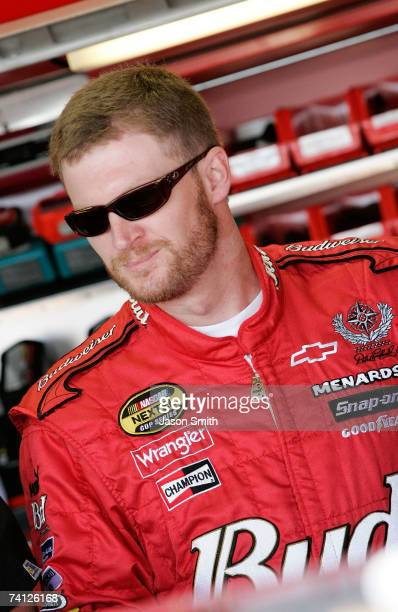 Dale Earnhardt Jr., driver of the Budweiser Chevrolet, stands in the garage prior to practice for the NASCAR Nextel Cup Series Dodge Avenger 500 on...