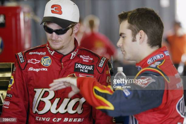 Dale Earnhardt Jr driver of the Budweiser Chevrolet talks with Jeff Gordon driver of the Hendrick Motorsports Dupont Chevrolet during practice for...