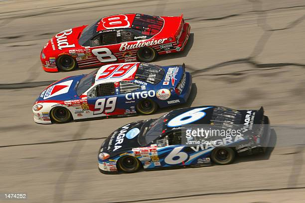 Dale Earnhardt Jr driver of the Chevrolet Monte Carlo races alongside Jeff Burton and Mark Martin on his way toward winning the NASCAR Winston Cup EA...