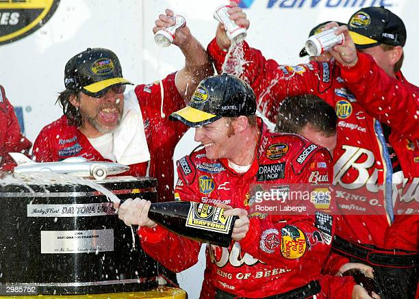 Dale Earnhardt Jr driver of the DEI Budweiser Chevrolet celebrates by spraying champagne in victory circle after winning the NASCAR Nextel Cup...