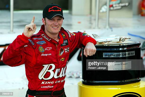 Dale Earnhardt Jr driver of the DEI Budweiser Chevrolet poses with the Harvey J Earl Daytona 500 Trophy in victory circle after winning the NASCAR...