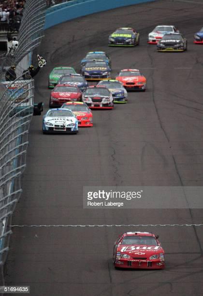 Dale Earnhardt Jr driver of the Earnhardt Enterprises Budweiser Chevrolet crosses the finish line to win the NASCAR Nextel Cup Series Checker Auto...