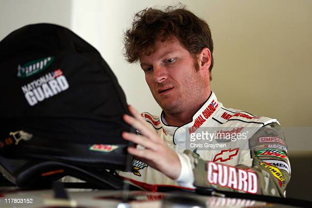 Dale Earnhardt Jr driver of the Guard Heritage / AMP Energy Chevrolet adjusts his helmet and hans device in the garage during practice for the NASCAR...