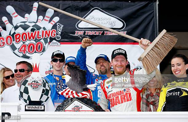 Dale Earnhardt Jr., driver of the Michael Baker International Chevrolet, celebrates in Victory Lane with a broom after winning the NASCAR Sprint Cup...
