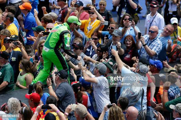 Dale Earnhardt Jr driver of the Mountain Dew Chevrolet shakes hands with fans before the Monster Energy NASCAR Cup Series FireKeepers Casino 400 at...