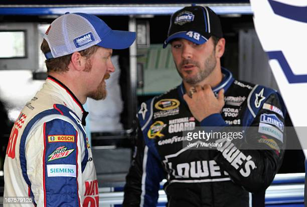 Dale Earnhardt Jr driver of the National Guard Chevrolet and Jimmie Johnson driver of the Lowe's Dover White Chevrolet stand in the garage during...