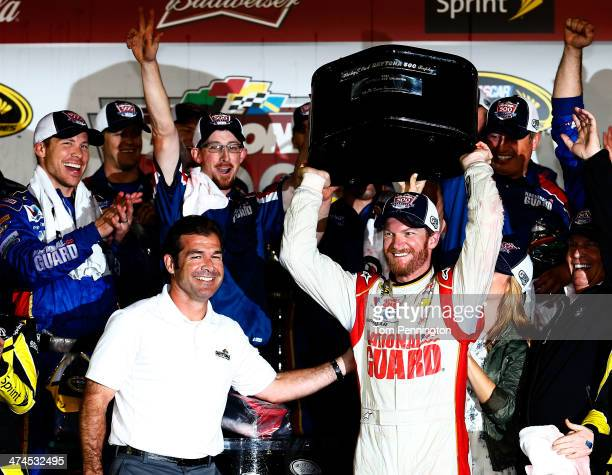 Dale Earnhardt Jr driver of the National Guard Chevrolet celebrates in Victory Lane with the Harley J Earl trophy and Joie Chitwood III after winning...