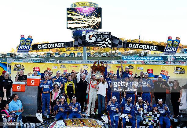 Dale Earnhardt Jr driver of the National Guard Chevrolet center poses with girlfriend Amy Reimann team owner Rick Hendrick and his team in Victory...