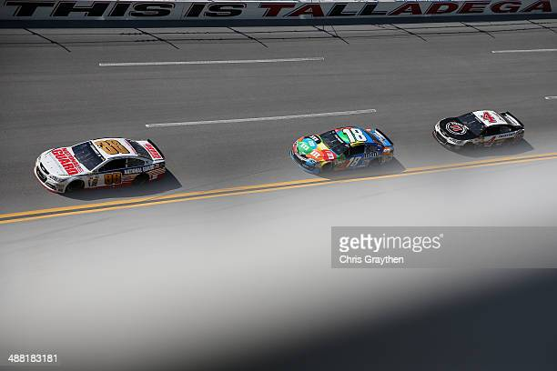 Dale Earnhardt Jr driver of the National Guard Chevrolet leads Kyle Busch driver of the MM's Pretzel Toyota and Kevin Harvick driver of the Jimmy...