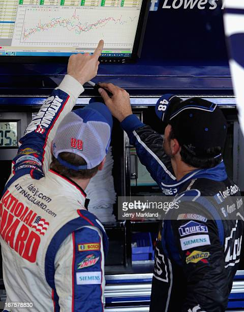 Dale Earnhardt Jr driver of the National Guard Chevrolet talks with Jimmie Johnson driver of the Lowe's Dover White Chevrolet during practice for the...