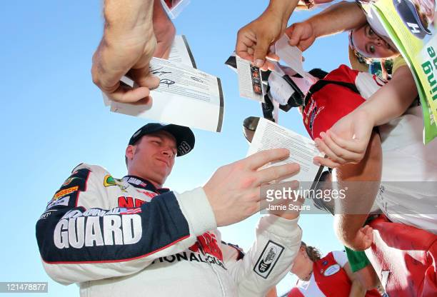 Dale Earnhardt Jr driver of the National Guard/Amp Energy Chevrolet signs his autograph for a fan during qualifying for the NASCAR Sprint Cup Series...