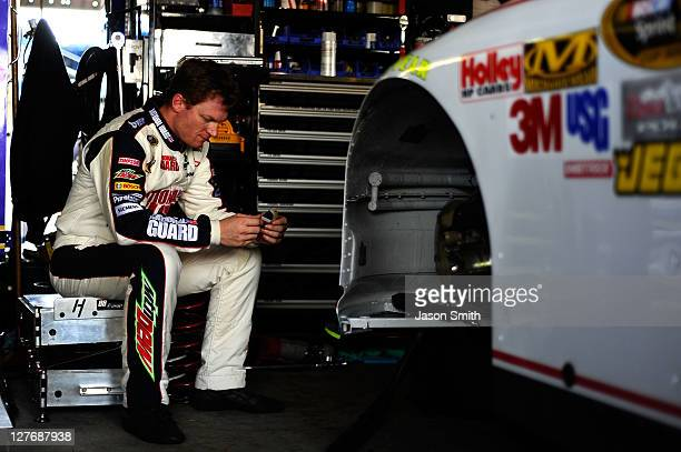 Dale Earnhardt Jr driver of the National Guard/Amp Energy Chevrolet reviews practice times in the garage area during practice for the NASCAR Sprint...