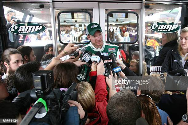 Dale Earnhardt Jr driver of the National Guard/AMP Energy Chevrolet talks to the media in the garage area during practice for the NASCAR Sprint Cup...