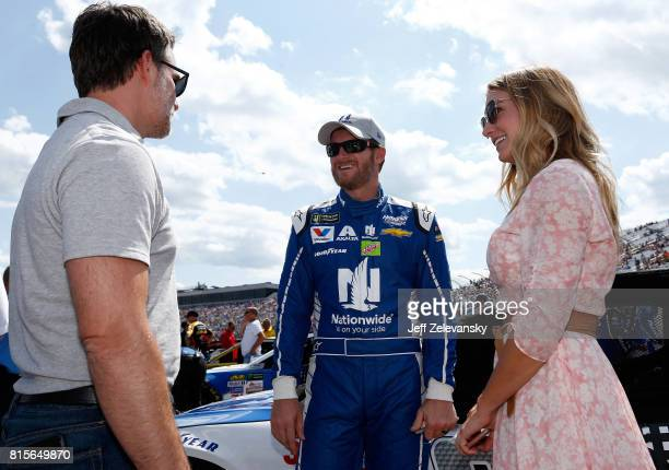 Dale Earnhardt Jr driver of the Nationwide Chevrolet and his wife Amy speak with former NASCAR driver Jeff Gordon on the grid prior to the Monster...