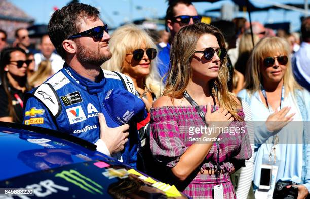 Dale Earnhardt Jr driver of the Nationwide Chevrolet and wife Amy stand during the national anthem prior to the 59th Annual DAYTONA 500 at Daytona...
