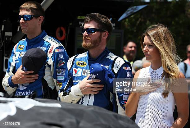 Dale Earnhardt Jr driver of the Nationwide Chevrolet center takes part in prerace ceremonies for with girlfriend Amy Reimann right and crew chief...