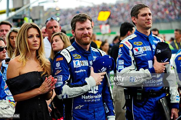 Dale Earnhardt Jr driver of the Nationwide Chevrolet center takes part in prerace ceremonies for with fiancee Amy Reimann left and crew chief Greg...