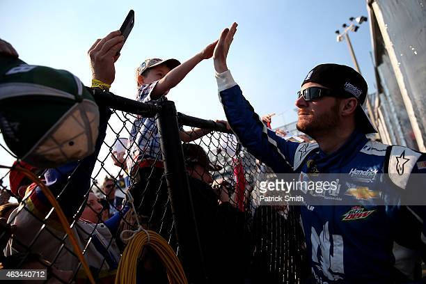 Dale Earnhardt Jr driver of the Nationwide Chevrolet interacts with fans in the garage area during practice for the 57th Annual Daytona 500 at...