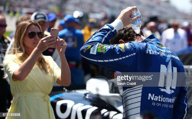 Dale Earnhardt Jr driver of the Nationwide Chevrolet pours water over himself as his wife Amy documents it prior to the Monster Energy NASCAR Cup...
