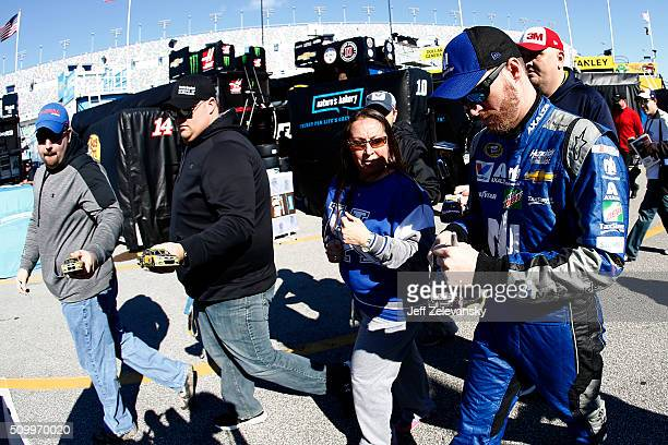 Dale Earnhardt Jr driver of the Nationwide Chevrolet signs autographs for fans in the garage area during practice for the NASCAR Sprint Cup Series...