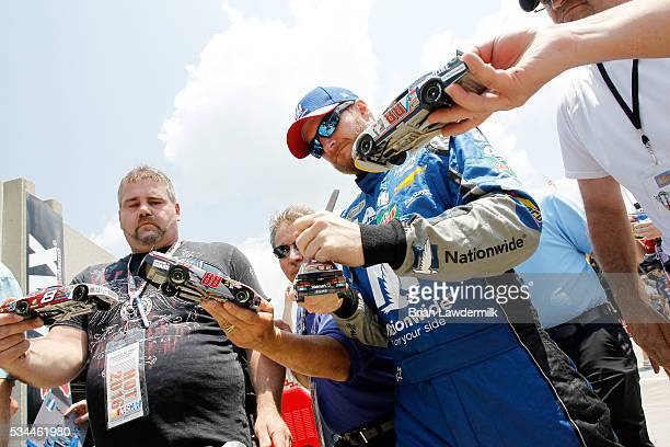 Dale Earnhardt Jr driver of the Nationwide Chevrolet signs autographs for fans during practice for the NASCAR Sprint Cup Series CocaCola 600 at...