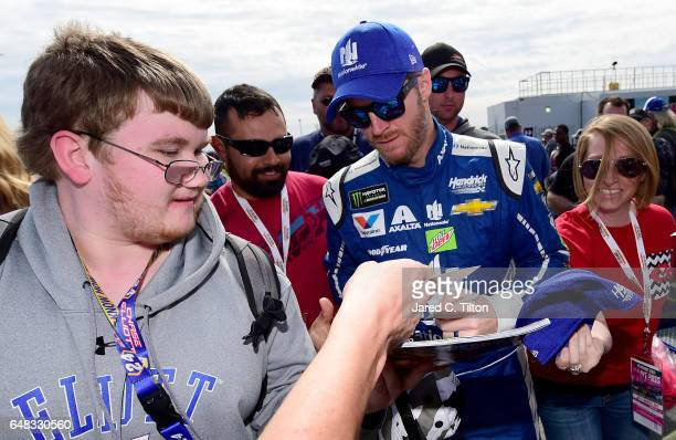 Dale Earnhardt Jr driver of the Nationwide Chevrolet signs autographs for fans prior to the Monster Energy NASCAR Cup Series Folds Of Honor QuikTrip...