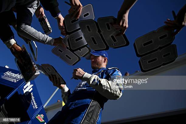 Dale Earnhardt Jr driver of the Nationwide Chevrolet signs his autograph for fans in the garage area during practice for the 57th Annual Daytona 500...