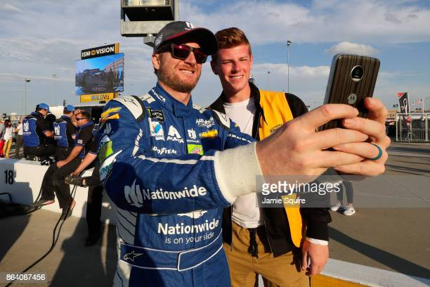 Dale Earnhardt Jr driver of the Nationwide Chevrolet takes a photo with a fan during qualifying for the Monster Energy NASCAR Cup Series Hollywood...