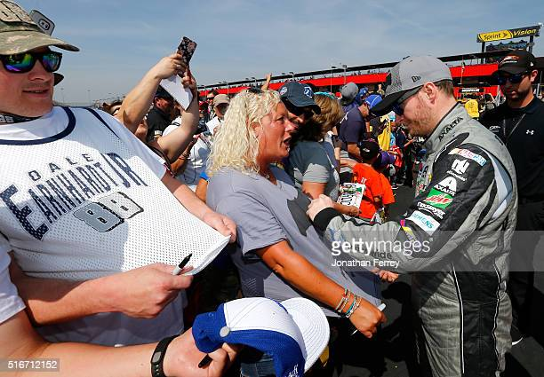 Dale Earnhardt Jr driver of the Nationwide Insurance / Batman Chevrolet signs an autograph for a fan before the NASCAR Sprint Cup Series Auto Club...