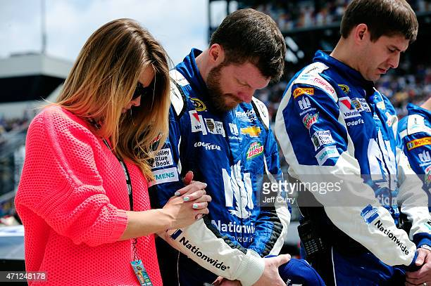 Dale Earnhardt Jr driver of the Nationwide Insurance Chevrolet stands with his girlfriend Amy Reimann during the national anthem prior to the start...