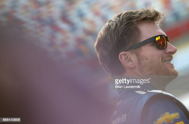 Dale Earnhardt Jr driver of the Nationwide Patriotic Chevrolet stands by his car during qualifying for the Monster Energy NASCAR Cup Series CocaCola...