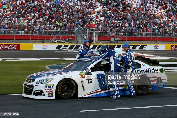 Dale Earnhardt Jr driver of the Nationwide Patriotic Chevrolet stands next to his car during a weather delay during the Monster Energy NASCAR Cup...