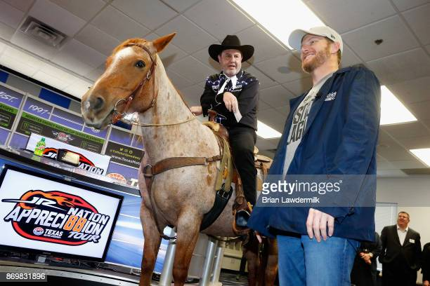 Dale Earnhardt Jr driver of the Nationwide/Justice League Chevrolet speaks with Texas Motor Speedway president Eddie Gossage during a press...