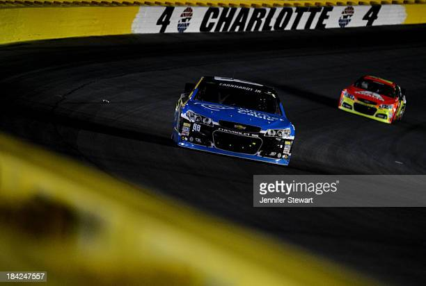Dale Earnhardt Jr driver of the Time Warner Cable Chevrolet leads Jeff Gordon driver of the Axalta Chevrolet during the NASCAR Sprint Cup Series Bank...